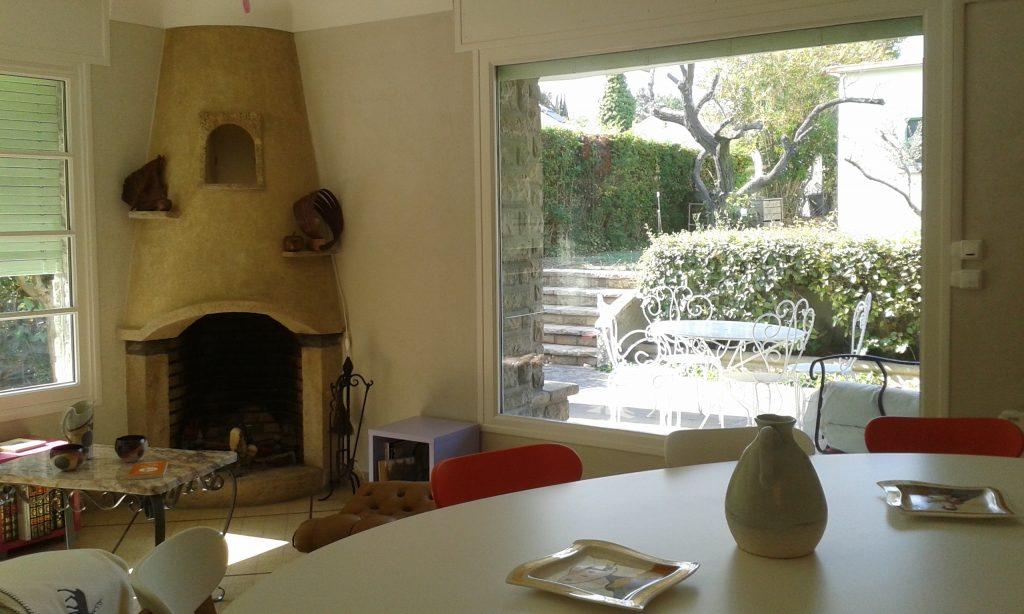 La cheminée et la baie vitrée sur le jardin